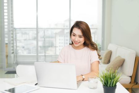 Young pretty Vietnamese woman working with laptop in office
