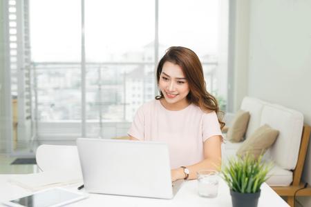 Joven bonita mujer vietnamita que trabaja con la computadora portátil en la oficina