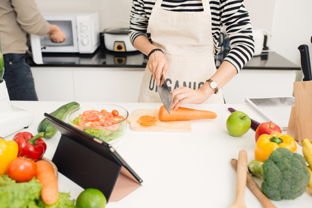 Young woman cutting vegetables in the kitchen. Stock Photo