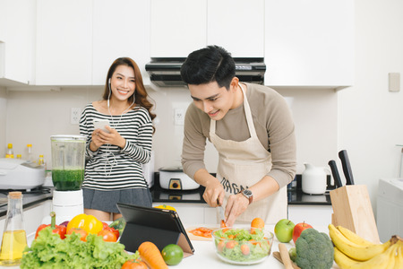 Asian woman with phone while a man prepares a meal