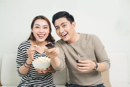 Emocionado pareja asiática joven viendo la televisión y comer palomitas de maíz Foto de archivo - 85210602