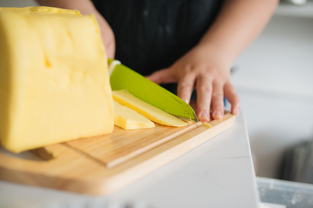 Cropped image of female chef cutting butter in kitchen