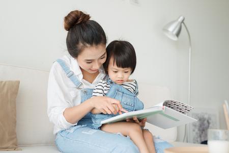 Glückliche liebevolle Familie. Recht junge asiatische Mutter, die ein Buch zu ihrer Tochter liest Standard-Bild