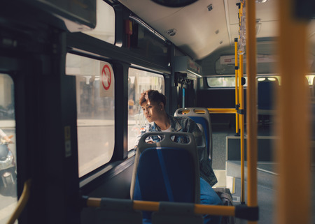 Asian man sitting dreaming on bus looking through window. Banco de Imagens
