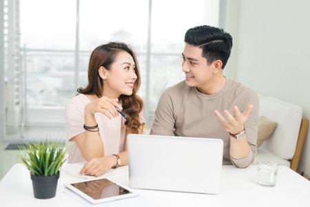 Gelukkige onderneemster en zakenman die laptop met behulp van op het werk in bureau