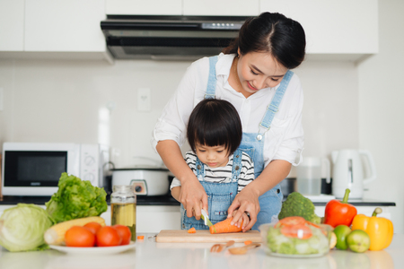 Happy family in the kitchen. Mother and child daughter are preparing the vegetables and fruit. Imagens