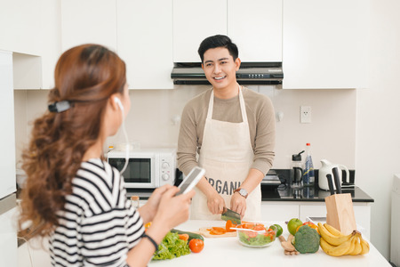 Woman using mobile phone in kitchen as boyfriend prepares meal Banco de Imagens