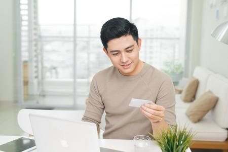 캐주얼 웃는 젊은 남자의 초상화는 신용 카드를 사용하여 지불하게