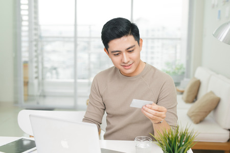 Portrait of a casual smiling young man make payment using credit card Standard-Bild