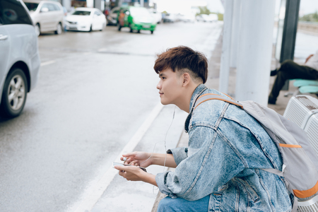 Young asian passenger waiting for taxi at the airport with phone Stock Photo