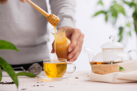 Cropped image of arista pouring honey into cup of tea Stock Photo