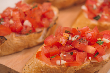 Tasty Italian bruschetta with bread topped with tomato and herbs on wooden board Stock Photo