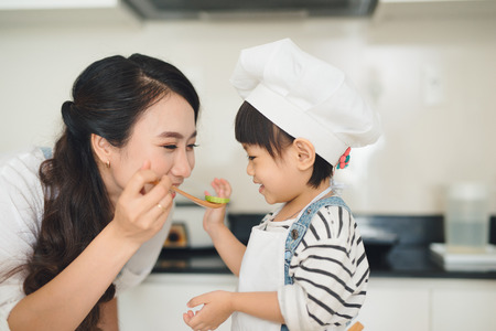 Happy family in the kitchen. Mother and child daughter are preparing the vegetables and fruit. Standard-Bild