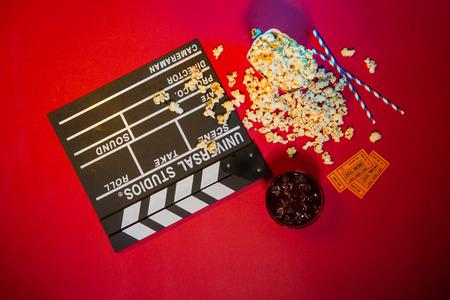 Cinema concept. Clapperboard, ticket and popcorn on red background Banco de Imagens