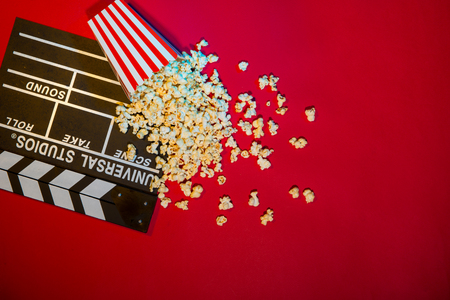 Cinema concept. Clapperboard, ticket and popcorn on red background Фото со стока