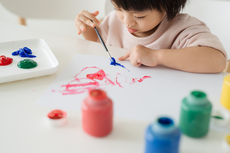 Little asian girl painting with paintbrush and colorful paints Zdjęcie Seryjne - 85333691