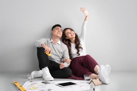 新しい家の設計を計画する flor に座っている若いアジアの大人のカップル。