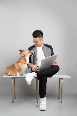 Handsome young businessman is using laptop while sitting with his dog o chair