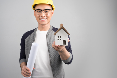 Businessman holding blueprints with an artificial model of the house