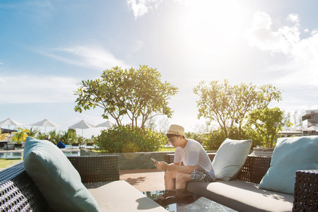 Asian man sitting on a sun lounger at a hotel on vacation Stock Photo