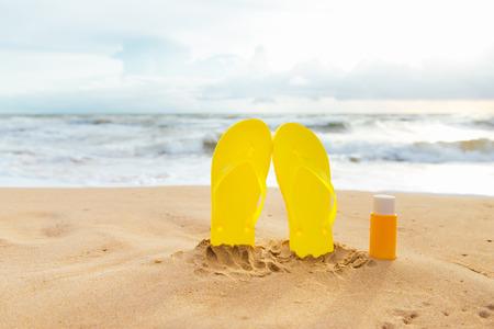 Summer sunbath. Sun lotion bottle in the sand