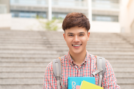 College asian male student holding book in campus