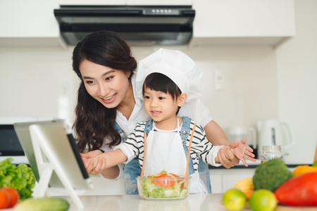 台所で彼女の娘と一緒に母が一緒に調理 写真素材