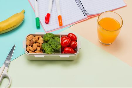 Schoolontbijt op bureau met boeken en pen aan boord van achtergrond Stockfoto