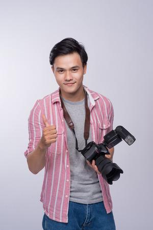 若いアジア写真家のスタジオで作業中のデジタル カメラを保持しています。