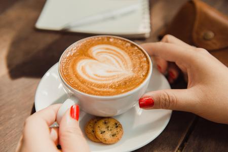 하트 모양으로 커피 한 잔 들고 여자
