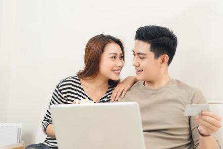 노트북 및 신용 카드를 사용 하여 젊은 아시아 부부 지불 온라인