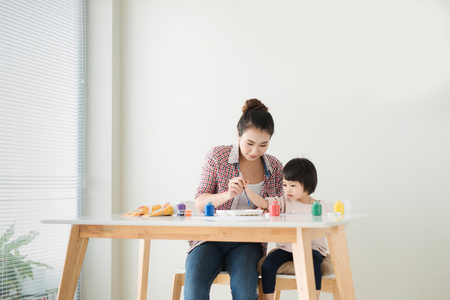 Happy family mother and daughter together paint. Asian woman helps her child girl. Stockfoto