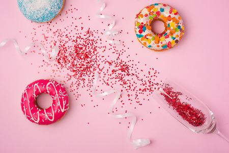 Flache Lage der Feier. Champagnerglas mit bunten Partyausläufern und leckeren Donuts auf rosa Hintergrund. Standard-Bild - 85841541