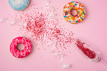 Flat lay of Celebration. champagne glass with colorful party streamers and delicious donuts on pink background. Stock Photo