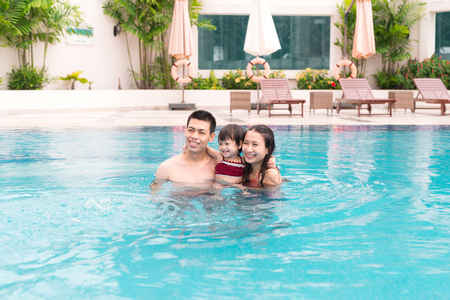 Vacation concept - happy family in a swimming pool Stock Photo - 85778583