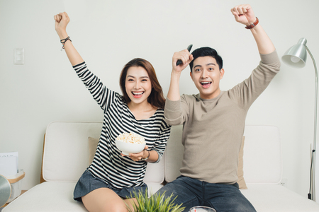 Excited young asian couple watching TV and eating popcorn