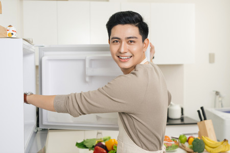 自宅のキッチンで食事の準備若いハンサムな男性