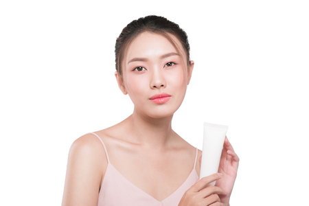 Beautiful asian woman. Beauty female face with perfect make up. Holding cream for body and face