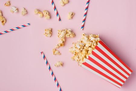 Popcorn in rode en witte kartonnen doos op de roze achtergrond.