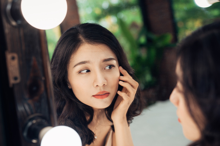 Beauty, skin care lifestyle concept. Young asian woman with acne looking at the mirror.