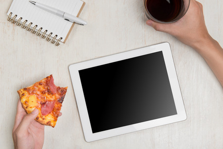 Man holding a digital tablet and tasty pizza with ingredients on wooden table.