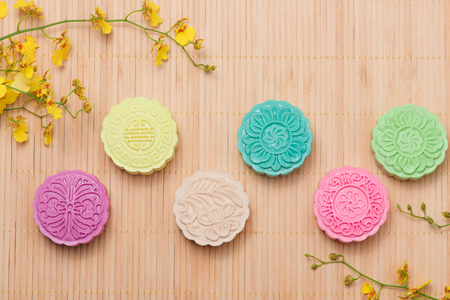 Colorful snow skin mooncake with tea pot on pink background