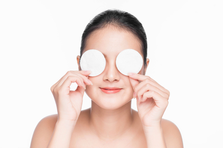 アジア人の少女は、綿のパッドを使用して顔肌リラクゼーションを気遣います。