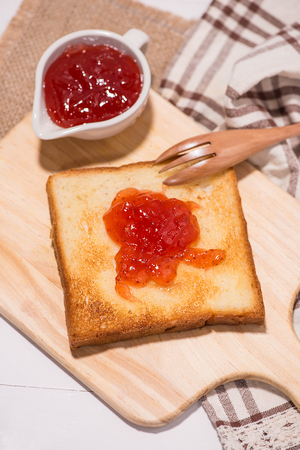Toast with strawberry jam on a plate on table.