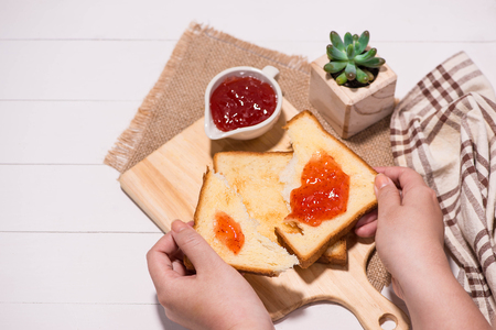 Woman hands eating bread with strawberry jam for breakfast. Focus on hands.