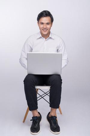 Slimme toevallige Aziatische mens gezet op stoel, die laptop op studioachtergrond met behulp van