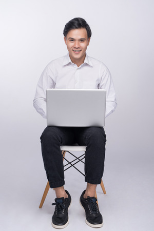 Smart casual asian man seated on chair, using laptop in studio background Banco de Imagens