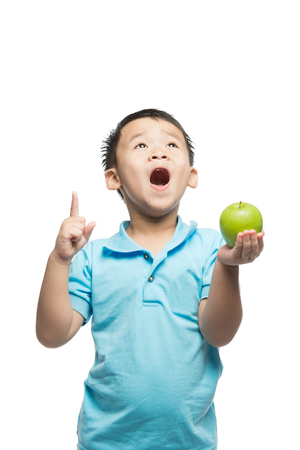Asian baby boy holding and eating red apple, isolated on white Imagens