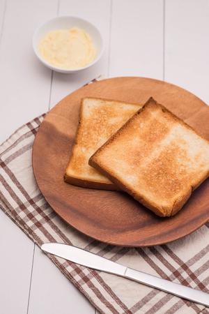 Close-up van plakje toast brood met boter op houten tafel Stockfoto