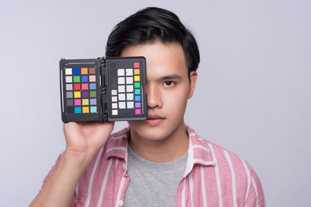 스튜디오에서 작업하는 동안 디지털 카메라를 들고 젊은 아시아 사진 작가 스톡 콘텐츠
